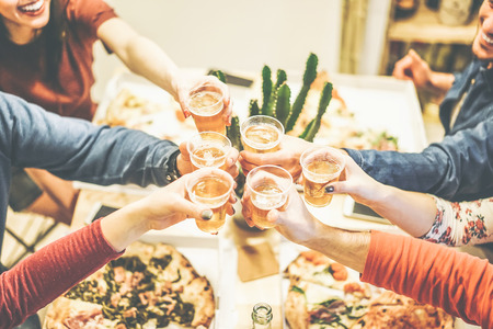 Group of friends enjoying dinner toasting with beers and eating take away pizza at home - Cheers of happy people drinking beer and having fun together -  Concept of friendship