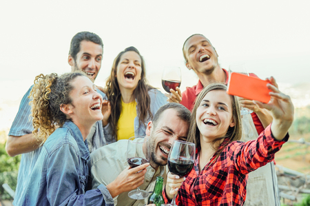 Group of happy friends taking selfie using mobile smart phone camera - Young people having fun a drinking red wine outdoor - Friendship, technology, youth lifestyle concept