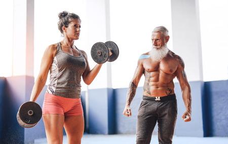Fit vrouw doet curl biceps oefening met halters in fitness gym center - vrouwelijke atleet training met haar persoonlijke trainer in wellness sportclub - training en sportieve motivatie concept