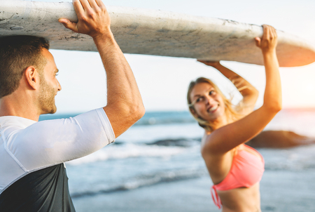 Happy loving couple holding a surfboard and looking each other - Friends having fun surfing during a vacation - People relationship, travel, sports lifestyle concept