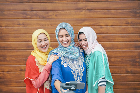 Happy muslim women making video with gimbal smart phone camera in college - Arabian young people having fun with new technology for social media - Millennials, generation z and religion concept