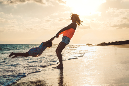 Happy loving family mother and daughter having fun on the beach at sunset - Mum playing with her kid next see in holidays - Concept of lifestyle family, parents and vacation Imagens