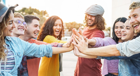Young friends stacking hands outdoor - Happy millennial people having fun joining and celebrating together - Friendship, empowering, teamwork, partnership and youth lifestyle concept Banco de Imagens