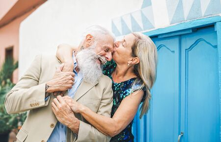 Happy fashion senior couple dating outdoor - Mature elegant older people celebrating date of their anniversary - Wife kissing her husband - Concept of love and relationship elderly lifestyle