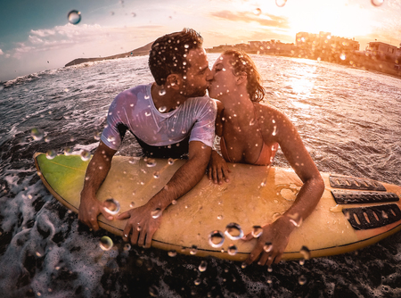 Happy romantic couple kissing while surfing in the ocean - Sporty surfers bodybording having a tender moment in the water  - Extreme sport, love, relationship and healthy lifestyle concept