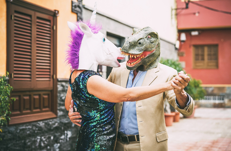 Crazy couple dancing and wearing dinosaur t-rex and unicorn mask - Senior elegant people having fun masked at carnival parade - Absurd, eccentric, surreal, fest and funny masquerade concept 版權商用圖片