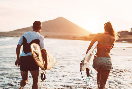 Happy surfer couple running with surfboards along the sea shore - Sporty people having fun going to surf together at sunset - Extreme surfing sport and youth relationship lifestyle concept Imagens