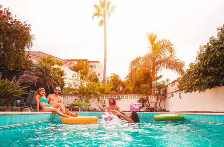 Group of happy friends relaxing in swimming pool - Young people having fun floating on air lilo during summer tropical vacation - Friendship, holidays and youth lifestyle concept Banco de Imagens