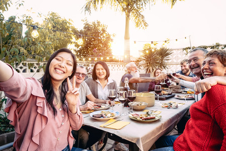 Happy family cheering and toasting with red wine glasses at dinner outdoor - People with different ages and ethnicity  having fun at bbq party - food and drink, retired and young people concept Stockfoto