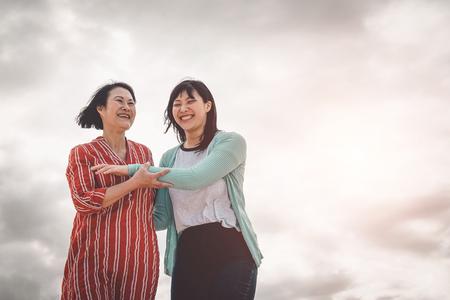 Asiatische Mutter und Tochter, die Spaß im Freien haben - Glückliche chinesische Familie, die draußen Zeit genießt - Glück, Liebe, Elternschaft und Lifestyle-Konzept