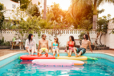 Group of happy friends relaxing in swimming pool - Young people having fun in exclusive summer tropical vacation - Friendship, holidays and youth lifestyle concept