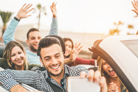 Happy friends taking photo selfie with mobile smart phone camera in convertible car - Young people having fun in cabriolet auto during their road trip vacation - Travel and youth lifestyle concept Stock Photo