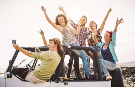 Happy friends taking selfie with mobile smart phone on convertible car - Millennial young people having fun making party during their road trip - Vacation, tech and youth holidays lifestyle concept