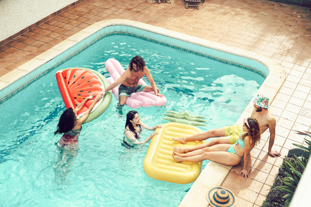 Happy friends having fun in swimming pool  during summer vacation - Young people relaxing and floating on air lilos in the pool resort - Friendship, holidays and youth lifestyle concept