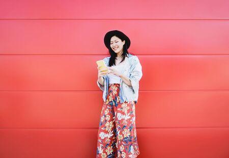 Fröhliches asiatisches Mädchen mit Handy im Freien - Chinesischer sozialer Einflussfaktor, der Spaß mit neuen Trends-Smartphone-Apps hat - Generation Z, Medien, Technologie und jugendlicher Lebensstil der Millennials Standard-Bild