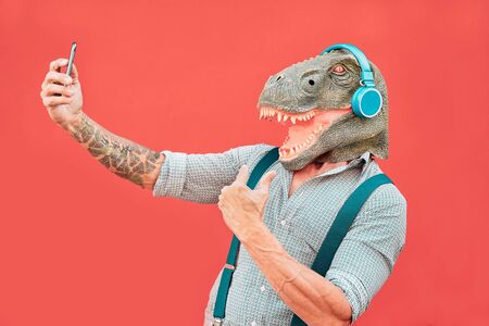 Crazy senior man wearing t-rex mask and taking selfie with mobile smartphone - Hipster older male having fun listening music and dancing outdoor -  Absurd, funny and surreal concepts Standard-Bild - 131407569