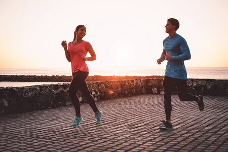 Fit couple jogging next the beach - Sporty young people doing run workout session outdoor - Healthy, youth and sport activity lifestyle concept Stock Photo
