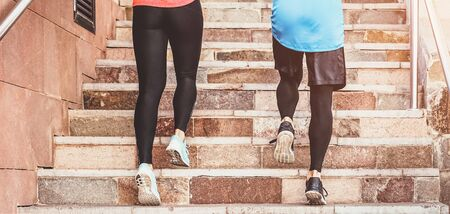 Close up runners legs training outdoor - Young couple doing a workout session on stairs outside - Health people, and sport lifestyle concept Stock Photo