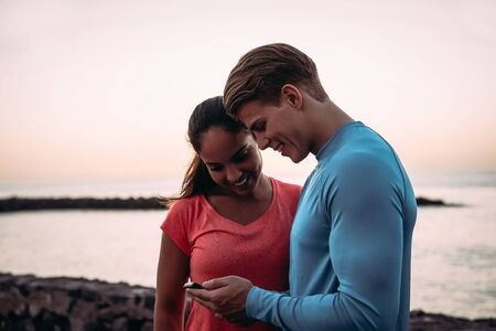 Young couple joggers having a break and using mobile smartphone outdoor - Sporty people having fun with trends technology apps for cellphone - Healthy, tech and youth lifestyle concept Stock Photo