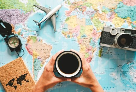 Top view of young woman planning her vacation using world map while drinking coffee - Tourist pointing the next travel destination - Concept of adventure, tourism, and traveling people lifestyle Stock Photo