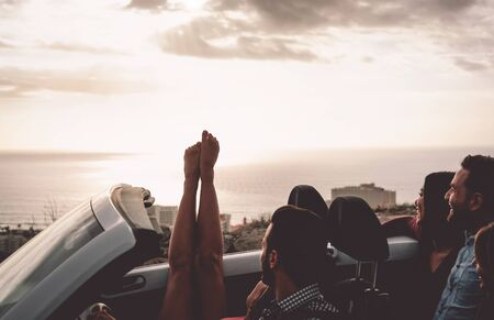 Happy friends driving on convertible car at sunset - Young people having fun during vacation road trip in cabriolet - Friendship, travel and youth lifestyle concept