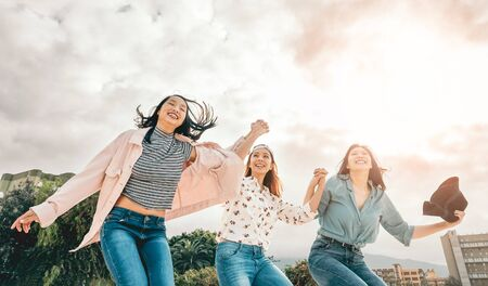 Happy Asian girls jumping outdoor - Young women friends having fun during university break - Millennial generation, friendship and youth people lifestyle 스톡 콘텐츠