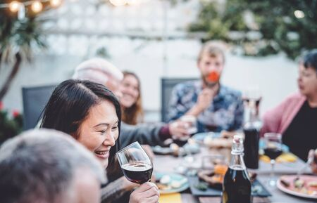 Happy family cheering and dining together outdoor - People with different ages and ethnicity having fun at barbecue dinner party - food and drink, retired and young people concept