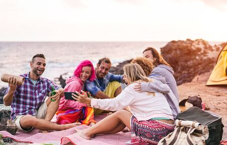Happy friends doing party at sunset while camping next the beach - Millennial young people having fun drinking beer and using mobile smartphone outdoor - Summer, vacation, tech and youth concept Standard-Bild - 134607523