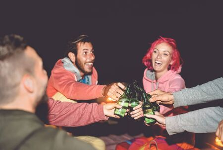 Happy friends toasting beers while camping outdoor - Group young people having fun making party together - Millennial generation and youth lifestyle culture holidays concept Standard-Bild - 134607549