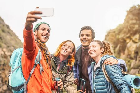 Happy friends taking photo selfie with mobile smartphone camera on mountains - Group young people trekking and having fun with new technology trends - Sport, hiking, Tech and social media concept Banco de Imagens
