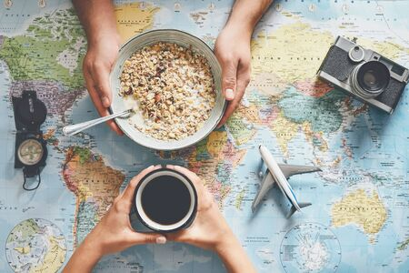 Top view hands people planning vacation with world map while doing breakfast with cereal milk - Couple getting ready for next world tour - Concept of adventure, tourism, and traveling people lifestyle Foto de archivo