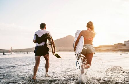 Happy surfers running in the water at sunset time - Young couple having fun surfing in ocean - Extreme sport and youth culture lifestyle concept