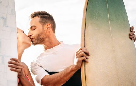 Happy surfers couple kissing before surfing in the ocean - Romantic lovers date having tender romance moments outdoor - Love relationship and sport people lifestyle concept