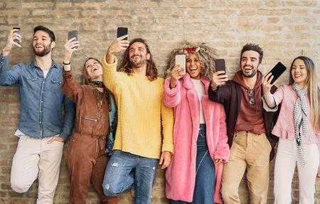 Amigos felices del grupo que toman selfie con el teléfono celular al aire libre - Gente joven de moda que se divierte con las nuevas aplicaciones de teléfonos inteligentes móviles para las redes sociales - Generación milenaria de la cultura juvenil y concepto de tecnología