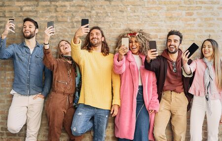 Happy group friends taking selfie with cell phone outdoor - Young trendy people having fun with new mobile smartphone apps for social media - Youth culture millennial generation and Technology concept