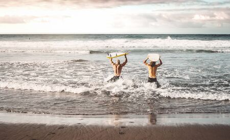 Happy fit friends having fun surfing on sunset time - People doing training exercises in school surfers - Sporty healthy lifestyle and extreme sport concept Stock Photo