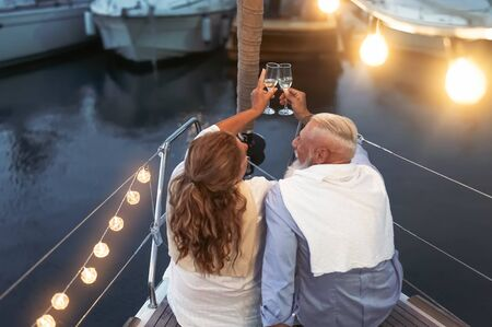Senior couple toasting champagne on sailboat vacation - Happy mature people having fun celebrating wedding anniversary on boat trip - Love relationship and travel lifestyle concept Stock Photo - 137394684