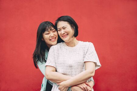 Glückliche asiatische Mutter und Tochter, die Spaß im Freien haben - chinesische Familienmenschen, die draußen Zeit miteinander verbringen - Liebes-, Beziehungs- und Elternschaftskonzept