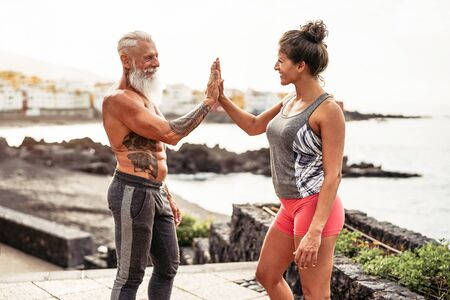 Fitness couple stacking hands during a workout day outdoor - Happy athletes motivating each other - Concept of people training, fit, empowering and bodybuilding lifestyle