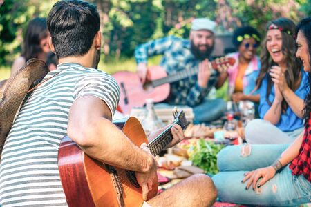 Young people doing picnic and playing guitar in park - Group of happy friends having fun during the weekend outdoor - Friendship, food and drink, funny activities and youth lifestyle concept Banco de Imagens