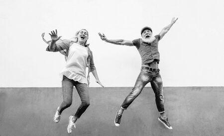 Happy crazy senior couple jumping together outdoor - Mature trendy people having fun celebrating and dancing outside - Concept of happiness, retired freedom, carefree, love and relationship
