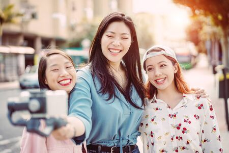 Happy Asian friends making video story in the city center - Trendy young people recording with gimbal smartphone outdoor - Friendship, technology, youth lifestyle and social media concept