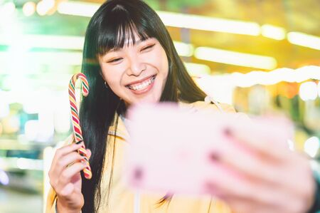 Asian girl taking selfie with mobile phone in amusement park - Happy woman having fun with new trends smartphone apps - Youth millennial people generation and social media addiction concept Stock Photo