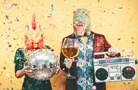 Crazy couple celebrating new year eve wearing chicken and dinosaur t-rex mask - Young trendy people having fun drinking champagne and listening music with vintage boombox - Absurd and holidays concept Banco de Imagens