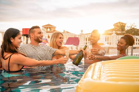 Happy friends toasting champagne at pool party  - Young people having fun drinking sparkling wine in luxury tropical resort at sunset - Summer holidays and vacation youth lifestyle concept Standard-Bild