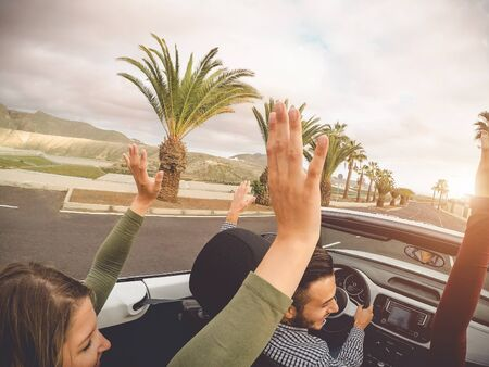 Happy friends having fun in convertible car on vacation - Young trendy people driving on cabriolet auto in summer road trip holidays - Transport and youth generation lifestyle concept