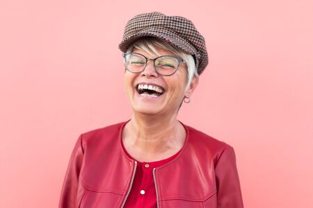 Happy senior woman having fun outdoor - Trendy mature person laughing and enjoying retired time - Elderly people lifestyle and mother's day concept - Coral Background Banque d'images - 144176989