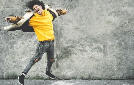 Afro American man having fun dancing in city center - Happy young guy jumping and enjoying positive moments - Millennial generation lifestyle and cool people attitude concept