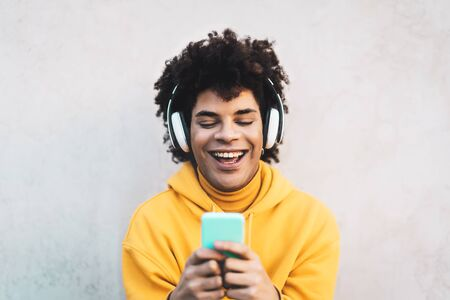 Happy Afro man using mobile smartphone outdoor - Young guy having fun listening music with wireless headphones outdoor - Youth millennial generation lifestyle and people addicted technology concept