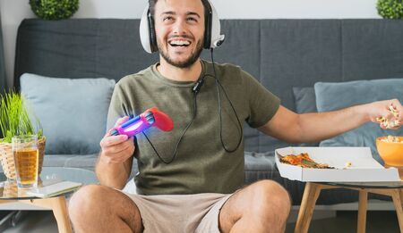 Happy man playing online video games - Young gamer having fun on new technology console - Gaming entertainment and youth millennial generation lifestyle concept